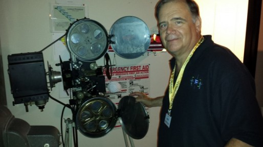 Projectionist Lou DiCrescenzo next to one of his beloved vintage projectors